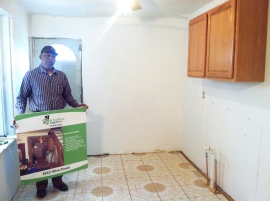 Theodus Lurry shows off his new kitchen cabinets and floor.